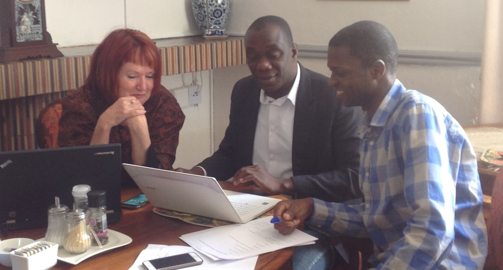 Diana Gibson and members of her Collaborative Working Group sitting around a laptop