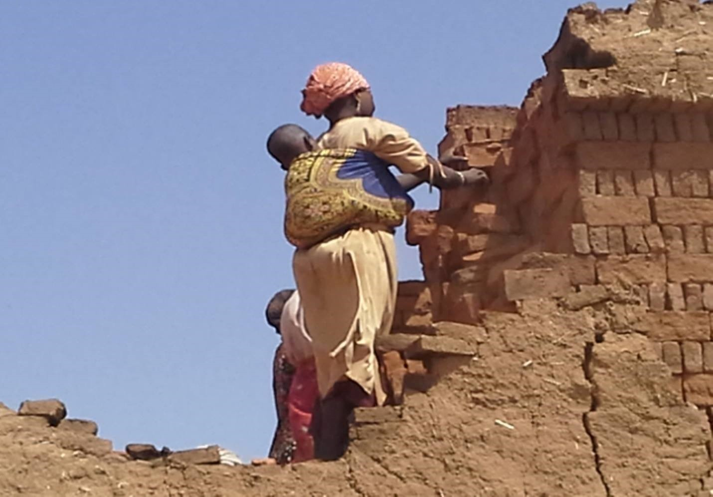 A woman working at a brick kiln while carrying her child at an IDP Camp near El-Fashier, Sudan