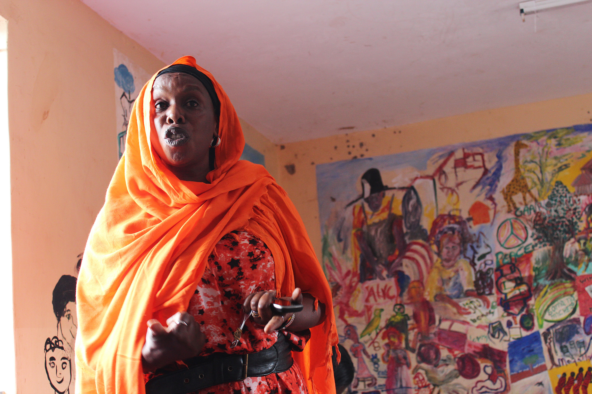 Woman speaking at a forum on Reducing Inter-ethnic Violence through Dialogue in Kenya with a wall of illustrations behind her.