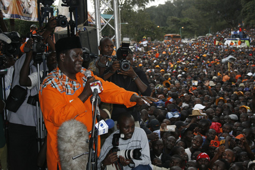 Raila Odinga address the crowd at Uhuru Park in Nairobi during a rally flanked with journalist behind him and the crowd below.