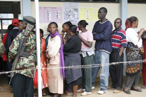 Over a dozen voters queue at a polling station in Langata while an armed guard stands by.