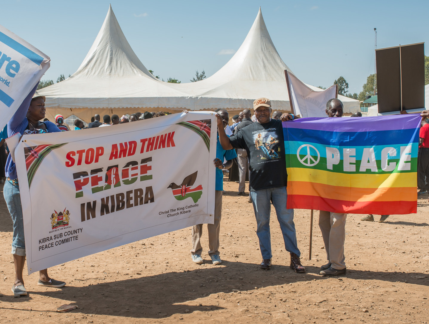 """Peace March in Kibera with signs saying """"Stop and Think Peace in Kibera"""" and """"Peace"""" on a rainbow background with a peace sign."""
