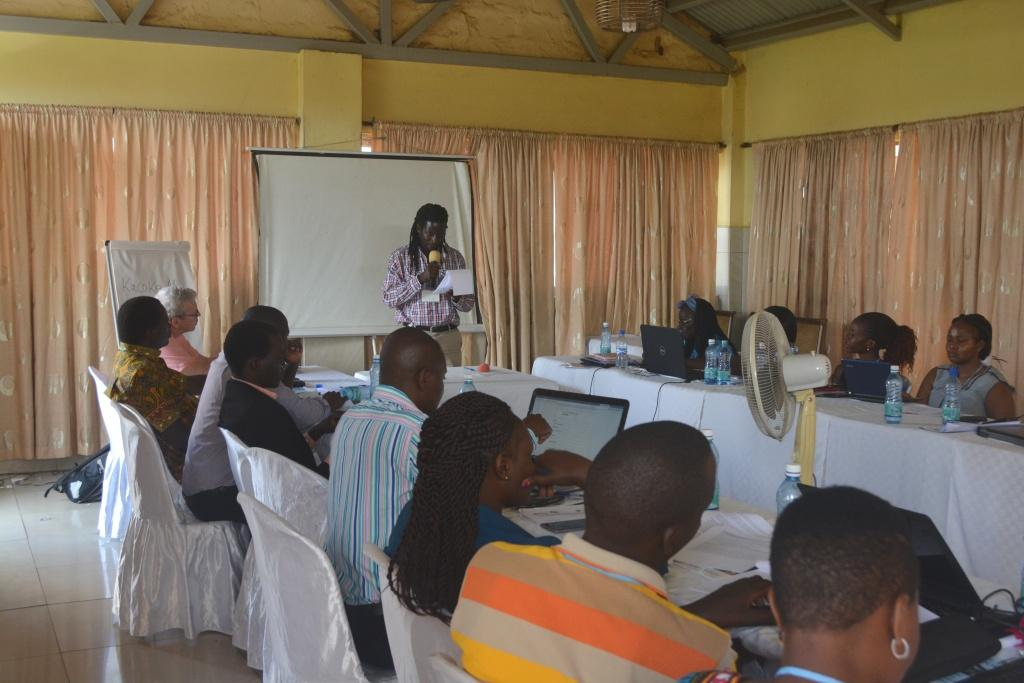 APN Alumnus Fredrick Ogenga at APN-sponsored Peace Journalism Workshop in Rongo, Kenya. Dr. Ogenga is standing and speaking in front of participants seated at horseshoe shaped conference table.