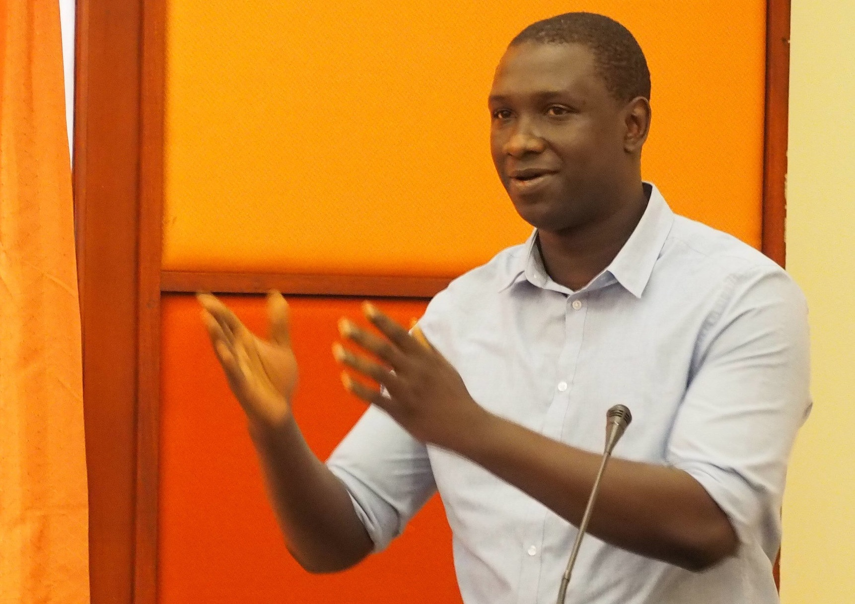 Dr. Ibrahim Bangura giving a presentation. Both hands are extended and there is an orange wall in the background.