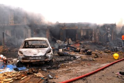 The wreckage of a charred vehicle remains in front of burning shops following a bomb blast at Terminus market in the central city of Jos on May 20, 2014. Twin car bombings on Tuesday killed at least 46 in central Nigeria in the latest in a series of deadly blasts that will stoke fears about security despite international help in the fight against Boko Haram Islamists. AFP PHOTO / STR